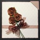 Kort i storleken 10x10 centimeter i brunt och vitt med tre rosor, brunt organzaband och fotohörn.