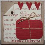 Julkort i vitt med rött paket och små hjärtan